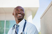 African American doctor standing outside looking up.
