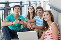 Teenagers sitting on outdoor stairway with laptop