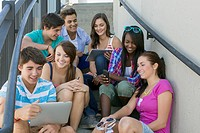 Teenagers on outdoor stairway using wireless technology