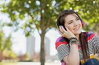 Pretty teenage girl listening to music in park (thumbnail)