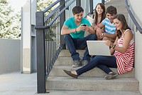 Teenagers sharing laptop on outdoor stairway