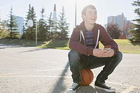 Teenage boy sitting on basketball in park