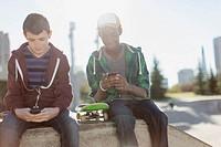 Teenage boys texting on smart phones at skate_park.