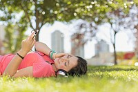 Teenage girl reclining on lawn in park listening to music