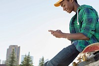 African American teenager outdoors texting on phone