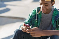 African American teenager texting on smart phone