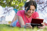 Teenage girl playing hand_held digital game in park