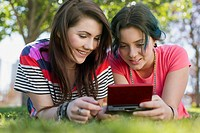 Teenage girls playing hand_held game in park