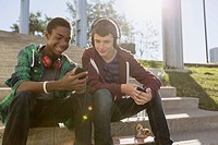 Teenage boys sharing music on smart phones