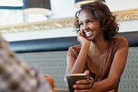Pretty, smiling, young adult woman in coffee shop (thumbnail)