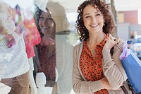 Pretty, middle_aged woman standing in front of store window