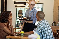 Young African American couple talking with coffee server
