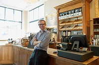 Coffee shop owner leaning against front counter