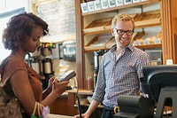 Coffee shop owner taking payment at check out