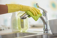 Woman's hands in rubber gloves polishing kitchen faucet