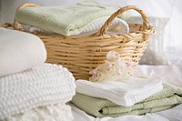 Folded towels and bedding in wicker basket