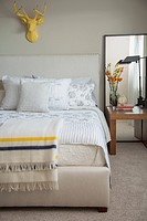 Contemporary bedroom with yellow deer head on wall