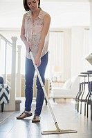 Woman dusting wooden floors in contemporary home
