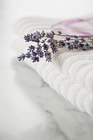 Close_up of lavender sprig on white towels.