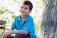 Cute six year old boy sitting outdoors by tree
