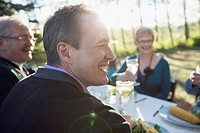 Adult son having a laugh with parents during outdoor meal