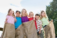 Cousins standing together with potato sacks on