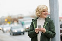 Mature woman texting on smartphone on city sidewalk.