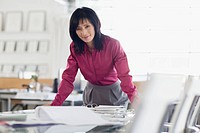 Pretty Asian businesswoman leaning on desk