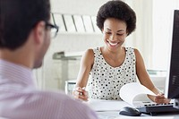 Pretty African American businesswoman smiling at her desk (thumbnail)