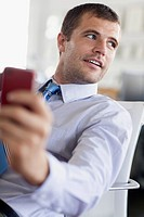 Handsome businessman with smartphone in office