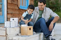 Father and young son painting birdhouse outdoors