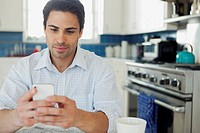 Mid-adult man texting on smartphone in kitchen.