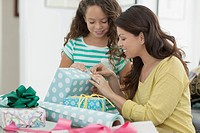 Mother and young daughter wrapping presents together