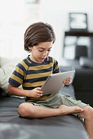 Four year old boy using pc tablet at home