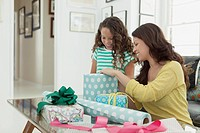 Mother and young daughter wrapping gifts in living room