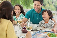 Family of four enjoying dinner together