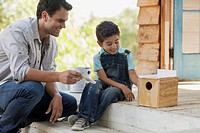 Father helping young son to paint birdhouse