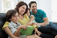 Young family of four sharing popcorn on movie night