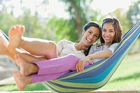 Portrait of preteen sister and older sister in hammock.