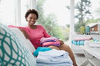 Portrait of mid_adult woman with folded laundry.