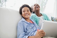 Sister and brother having a laugh browsing pc tablet