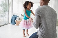 Young girl in tutu dancing with her dad.