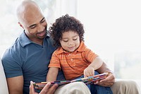Toddler sitting in father's lap with book