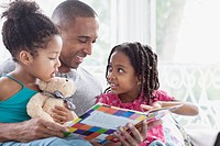 Father reading to his two young daughters
