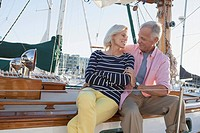Senior couple cuddling on sailboat (thumbnail)