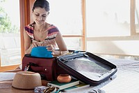 Mid_adult woman packing up suitcase