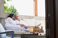 Couple in robes talking on outdoor patio