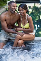 African American couple sharing a laugh by pool