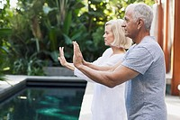 Senior couple doing Tai chi by pool