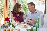 Man surprising woman with ring at dinner